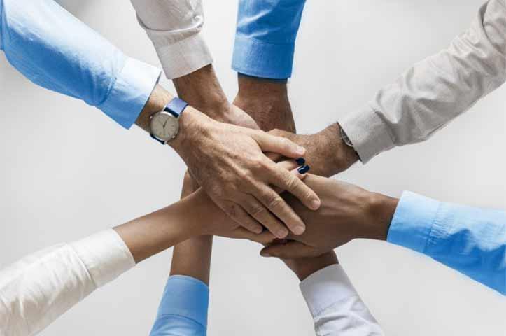 Wir sind ein Team Hände übereinander legen